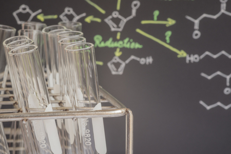 biochemist: Test tubes in front of blackboard with color chemical formula