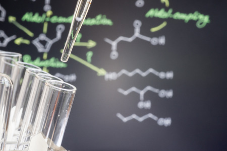 spectrometry: Adding sample into test tube in front of blur chemical formula Stock Photo