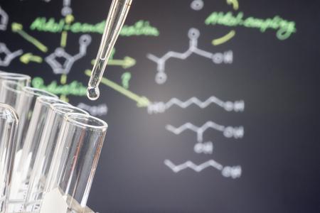 Reflet de formular chimique dans la goutte d'eau sur le tube d'essai en face de formule chimique de flou