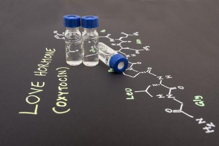 oxytocin: Close-up blue cap sample vial on paper with chemical formula of Oxytocin (love hormone)