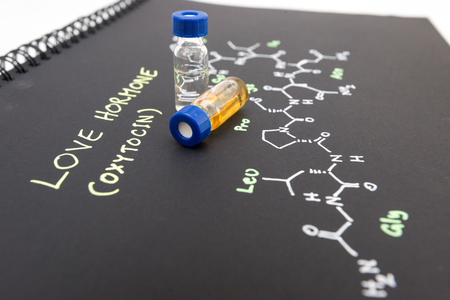 oxytocin: Close-up blue cap sample vial on notebook with chemical formula of Oxytocin (love hormone)