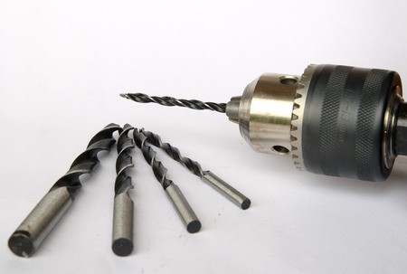 bit background: drill and drill bit on white background Stock Photo