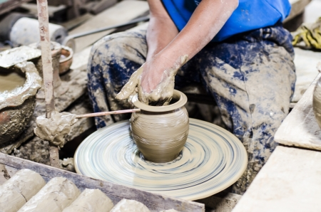 Man hands working with a pottery wheel. photo