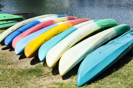 A row of multi colored kayaks lined up on riverbank. photo