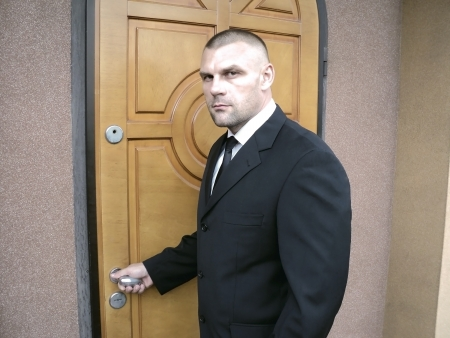 The man, dressed in a black suit, opens the front door of the house photo