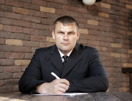 Focused man in a dark suit holding a pen in his hand while sitting at a wooden table against a brick wall Stock Photo - 19794465