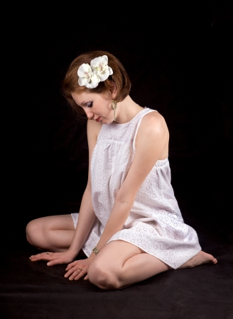 Red-haired girl with ornaments in white dress on a black background photo