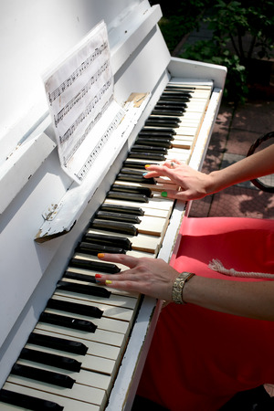Female hand with red fingernails on the keys of the old white piano photo