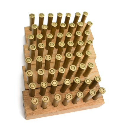 stored: Old revolver cartridges stored in wooden blocks on a white background Stock Photo