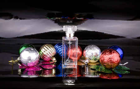 christmas perfume: Womens perfume bottle with colored Christmas balls on a black background Stock Photo