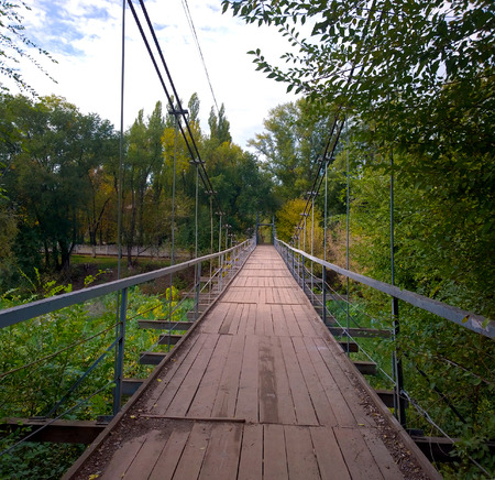 Suspension bridge with a wooden transition in the fall in the city of Krivoy Rog in Ukraine