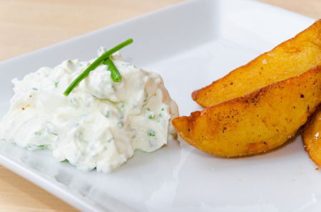 bratkartoffeln: Creamy dip on white plate with fried potatoes