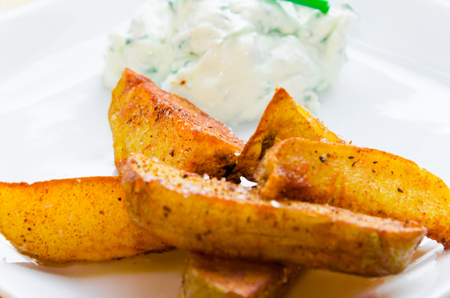 fried potatoes: Detail on fried potatoes with creamy dip on white plate Stock Photo