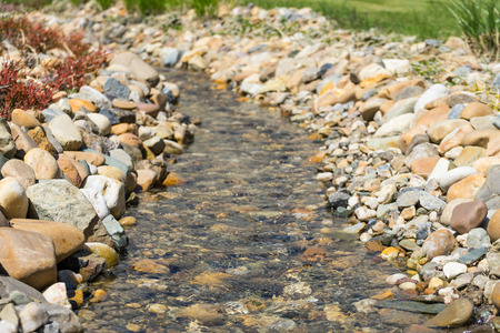 bourn: Small calm stream. Stream surrounded by rocks. Soft focus. Small river close up. Stones and rocks with stream. Stock Photo
