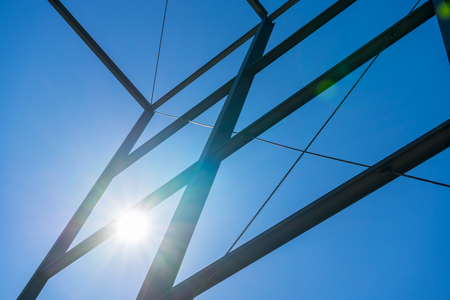 steelwork: Steel construction with sky background and shining sun. Sun beams. Modern business building construction. Sun burst on blue sky with steel construction. Stock Photo