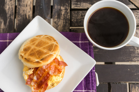 bacon and eggs: Salt muffin with scrambled eggs, bacon and cheese on white plate with dark coffee in white mug lying on wooden background. Unhealthy breakfast with bacon, eggs, pastry and coffee on purple dishtowel. Flat view.