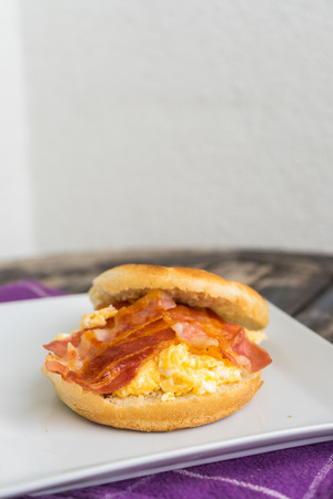 dishtowel: English breakfast. Salt muffin with scrambled eggs, bacon and cheese on white plate lying on wooden background. Unhealthy breakfast with bacon, eggs and pastry on purple dishtowel. Stock Photo