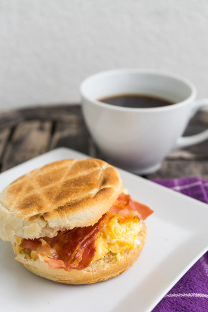 dishtowel: English breakfast. Salt muffin with scrambled eggs, bacon and cheese on white plate with dark coffee in white mug lying on wooden background. Unhealthy breakfast with bacon, eggs, pastry and coffee on purple dishtowel. Stock Photo