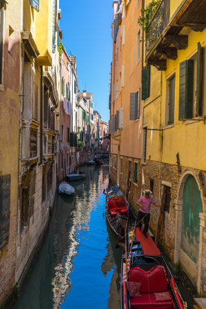 gondolier: VENICE, ITALY - May 23, 2016: Gondolier taking care of two anchored gondolas in Venice canal with clear sky between colorful buildings. Editorial