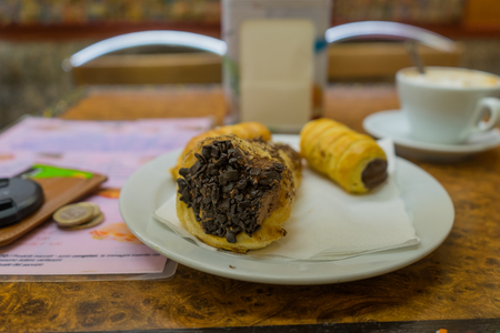 euro coins: Chocolate cannoli on white plate with coffee, euro coins and wallet on background in soft focus. Cannoli on white plate in Venice. Soft focus.