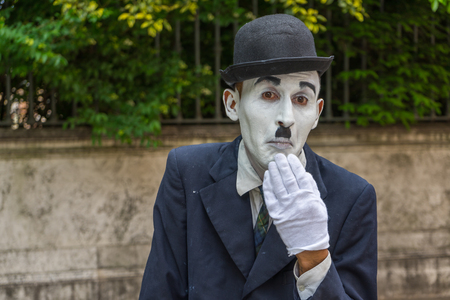 chaplin: VENICE, ITALY - May 24, 2016: Male mime looking like a Charlie Chaplin in Venice with white glove and dark hat. Street male mime entertaining tourists.
