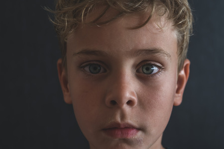 desaturated: Close up portrait of young sad or depressed blonde boy with blue eyes. Unsaturated, vintage with cinematic look young man detail portrait.