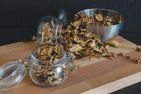 Vintage styled photo of sliced, chopped and dried various mushrooms in preserving glass and silver bowl standing on wooden desk on dark structured background.