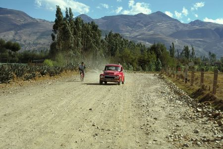 dusty: A wonderful red old timer overtakes a bicycle on a dusty road near Cajamarca, Peru