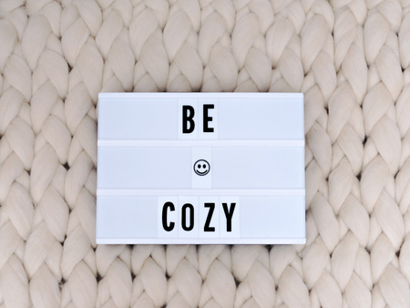 BE COZY word on lightbox on knit background. Cozy compozition. Knit background.