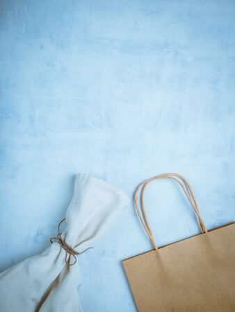 Recycled paper shopping bags on light brown background.