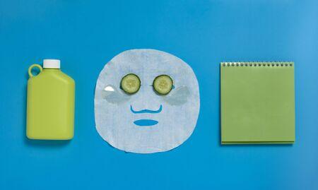 Face mask, reusable water bottle, cucumber, notepad on blue background. Dehydration. Foto de archivo