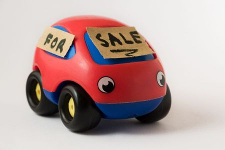 Small car toy with a for sale signboard, on a white background photo