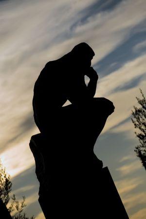 """denker: Een beroemde Auguste Rodin's beeld """"De Denker"""", een man zitten in een denken positie, met de hand op de kin. Hier met tegenlicht geschoten, als een silhouet, genomen in Saint Paul de Vence, op de Franse Riviera."""