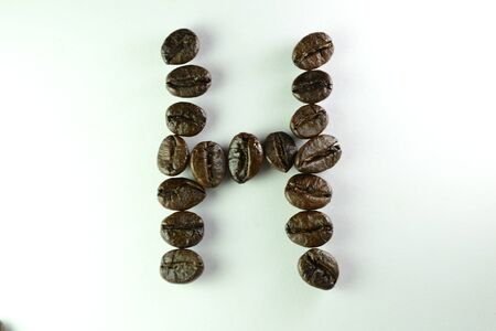 Coffee Beans, the alphabet H is formed with coffee beans in white background Banco de Imagens