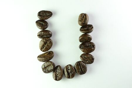 Coffee Beans, the alphabet U is formed with coffee beans in white background Banco de Imagens