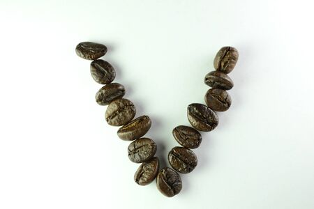 Coffee Beans, the alphabet V is formed with coffee beans in white background