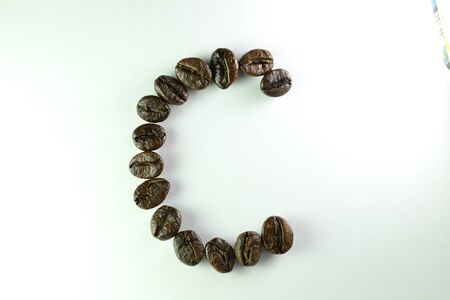 Coffee Beans, the alphabet C is formed with coffee beans in white background