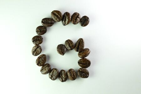 Coffee Beans, the alphabet G is formed with coffee beans in white background Banco de Imagens
