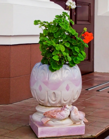 Geranium flowers growing in a pot, decorated with figures of two doves  photo