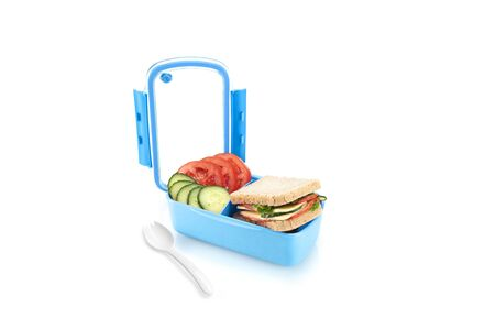 Healthy blue lunch box with sandwiches and vegetables for kids. Isolated on white background.