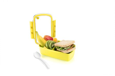 Healthy yellow lunch with sandwiches and fruits for kids. Isolated on white background.