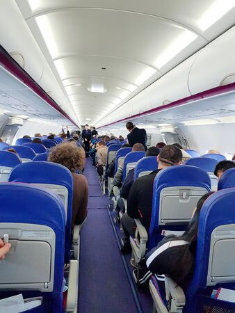 Interior of an airplane with passengers on seats waiting to take off.