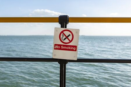No Smoking Warning Sign in front of blue sea.