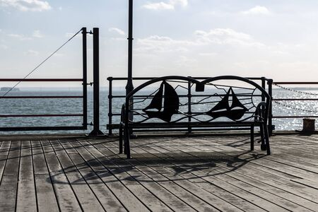 Metal Bench in Front of a Sea or Lake.