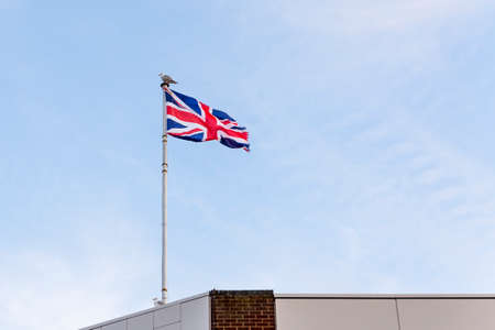 Flag of the United Kingdom, Flag of England embroidered on blue sky on the roof of a building.