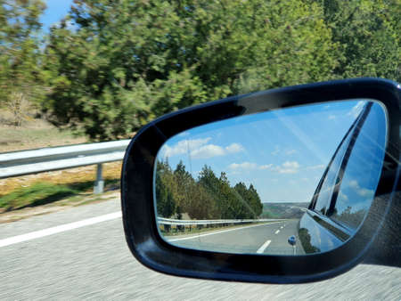 Landscape and road reflection in car rearview black mirror.