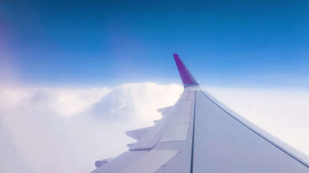 Flying over the clouds. View from plane aircraft passenger window. Clouds and skyline horizon panoramic view. Foto de archivo