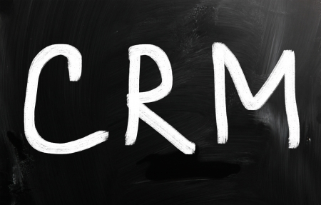 definition define: The word  CRM  handwritten with white chalk on a blackboard