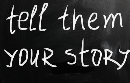 Tell them your story handwritten with white chalk on a blackboard