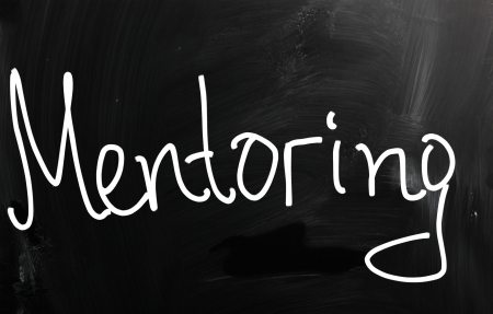 perceived: The word Mentoring handwritten with white chalk on a blackboard